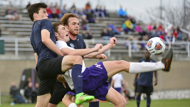 University of Evansville midfielder Ian McGrath scores a goal between two defenders from the Saint Louis FC reserve team at Arad McCutchan Stadium in March. Saint Louis FC won, 2-1.