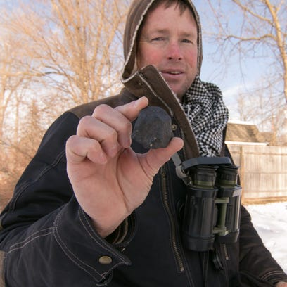 Robert Ward holds the largest of three meteorites he's
