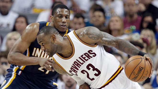 Cavaliers' LeBron James (23) drives past  Pacers' Thaddeus Young (21) in the second half in Game 1.