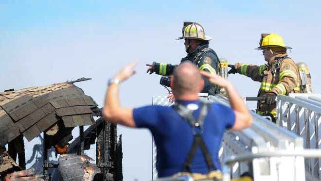 Firefighters point toward the top of the smoldering house off Bayberry Lane in Keen-wick by the Bay that caught fire Monday, Feb. 1.
