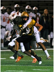 Abilene High School wide receiver Wes Berry gets wrapped-up by Haltom High School Imiee Cooksey during Friday's game Sept. 29, 2017. Abilene lost, 35-36.