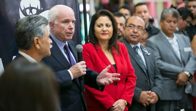 Sen. John McCain, R-Ariz., second from left, speaks at Mercado de Los Cielos inside Desert Sky Mall in Phoenix. McCain announced a Hispanic coalition supporting his re-election, but his record on immigration and border issues has come under scrutiny.