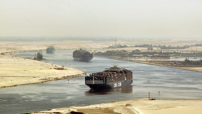Cargo ships sail through the Suez Canal near Ismailia, Egypt. Terroriststried to disrupt navigation in the waterway by targeting a Panama-flagged ship.