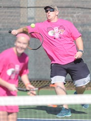 Abilene firefighter Brent Holsenbeck, back, hits a shot while teammate Katherine Morris, an Abilene High sophomore, looks on in their match against fellow firefighter Jonathan Bowen and AHS sophomore McKenna Bryan. The teams were playing in the AHS-Cooper Hurricane Harvey relief fundraiser Saturday, Jan. 27, 2018 at Rose Park Tennis Center.