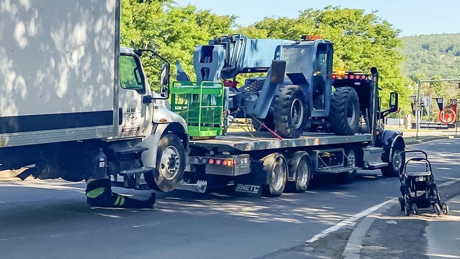 A truck, left, that officials said was involved in a vehicle-pedestrian incident is prepared to be towed from Centerway early Wednesday. A stroller, from a child involved in the collision, sits on the curb at right.