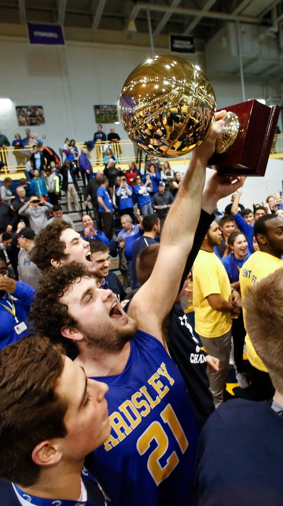 Ardsley's Julian McGarvey (21) center hoists the gold