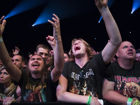 Fans cheer as Iron Maiden performs during the band's