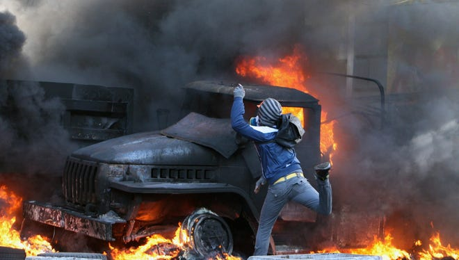 A protester throws a device at riot police during continuing protests in downtown Kiev.