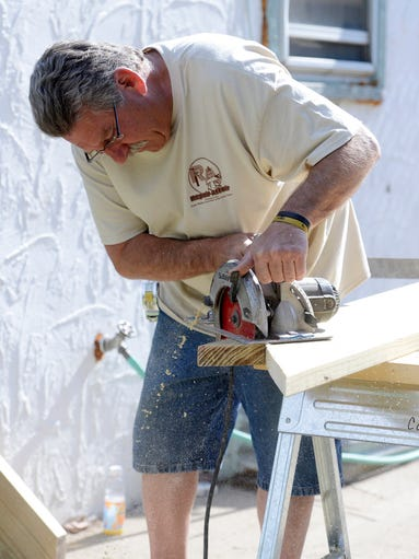 Mike Metzger cuts a board while making steps for a deck at a home on South West Ave. Tuesday as part of the annual Repair Affair, a community service project for the Home Builders Association of the Sioux Empire, June 10, 2014.
