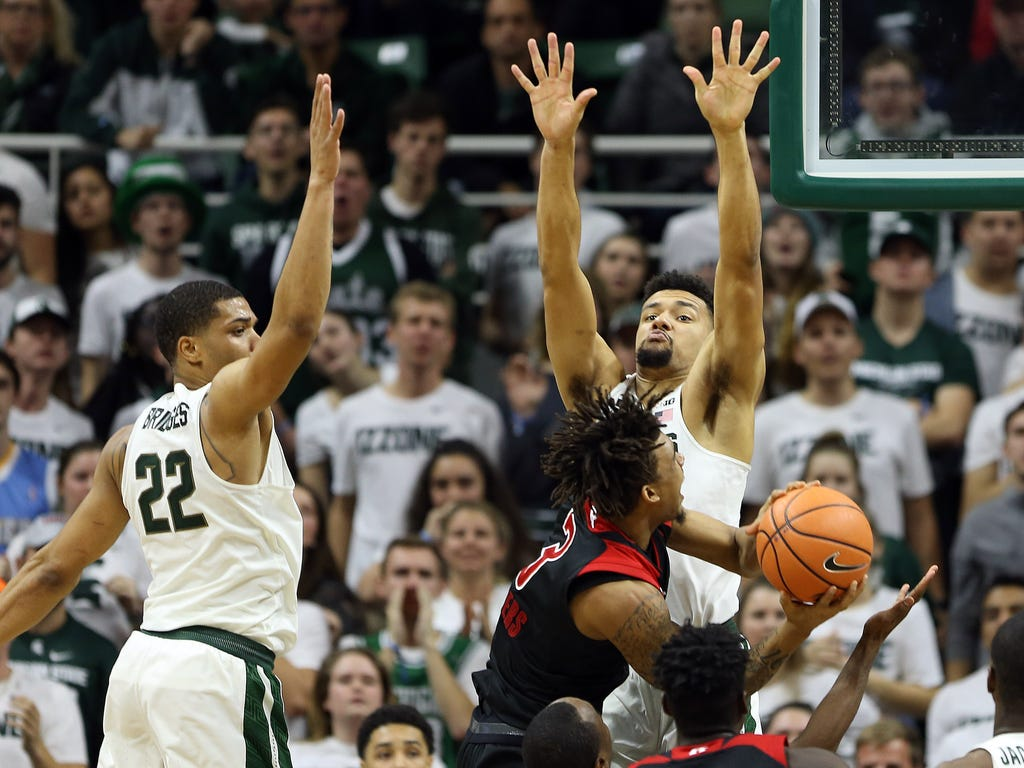 Rutgers Scarlet Knights guard Corey Sanders is defended by Michigan State Spartans forward Kenny Goins, right, and guard Miles Bridges during the second half of a game at Jack Breslin Student Events Center in East Lansing, Mich.