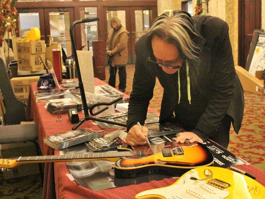 Musician Todd Rundgren signs a guitar before his concert