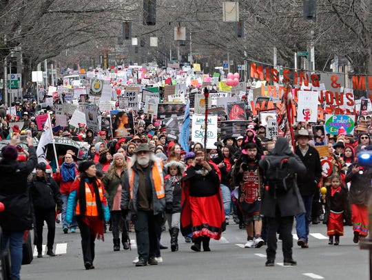 Marchers fill a street in downtown Seattle during a