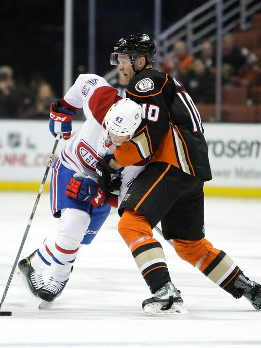 Montreal Canadiens' Daniel Carr, left, is checked by Anaheim Ducks' Corey Perry during the first period of an NHL hockey game Tuesday, Nov. 29, 2016, in Anaheim, Calif. (AP Photo/Jae C. Hong)