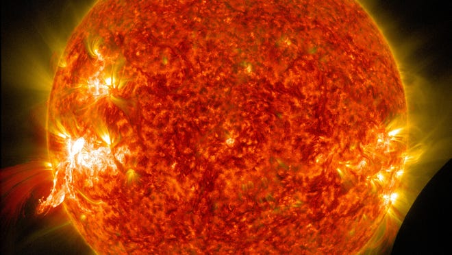 A solar flare erupts on Jan. 30, 2014, on the left side of the sun, captured by NASA's Solar Dynamics Observatory. In the lower right corner, the moon can be seen, just between the observatory and the sun.