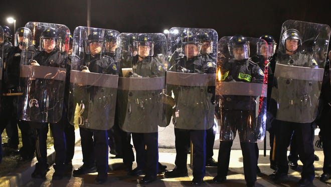 Officers guard the Ferguson (Mo.) Police Department on Monday.