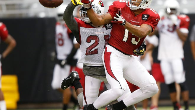 Cardinals CB Patrick Peterson breaks up a pass inteneded for WR Michael Floyd during training camp at University of Phoenix Stadium in Glendale, Ariz. July 30, 2014.