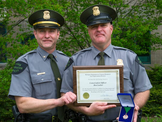 Michigan Department of Natural Resources' Law Enforcement Division Chief Gary Hagler (left) presents a lifesaving award to Conservation Officer Ben Lasher (right).