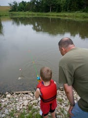 A father-son team brings in a fish from a pond.