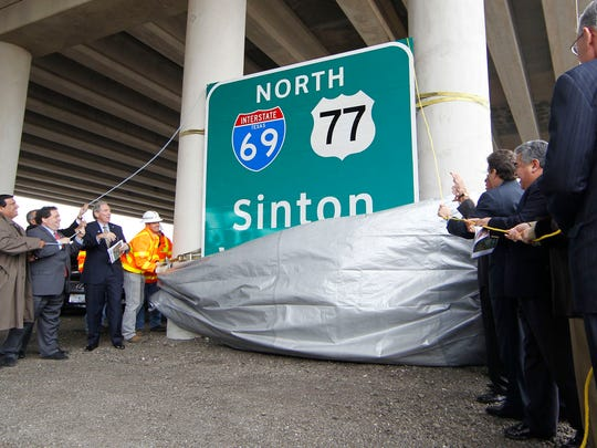 City, state and federal officials unveil a 10 foot by 10 foot highway sign marking the first segment of Interstate 69 in Texas in 2011under the US 77 overpass in Robstown.