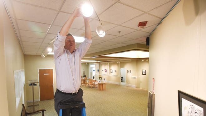 Rob Cook of the Muskingum County Library System trains a spotlight on a piece of work in the The PowerHouse of Southeastern Ohio Juried Student Art Show in the Carnegie Wing of the John McIntire Library in Zanesville. The show opens on Friday.