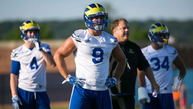 Linebacker Troy Reeder (9) and his younger brother Colby (4) listen to instructions during their first day at University of Delaware preseason football practice on Friday.