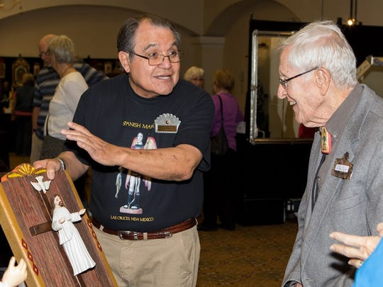 Artist Rodolfo Parga shows his art piece to J. Paul Taylor Saturday at the Spanish Market event at Hotel Encanto.