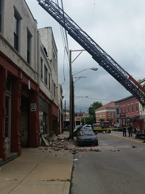 A sign and several bricks detached from the top of a building on West Pike Street in Covington and landed on the sidewalk and a Honda.