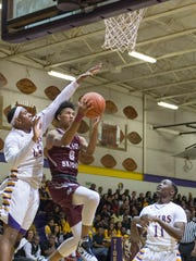 Breaux Bridge's Ignatius Patt (0) for Breaux Bridge drives to the basket and gets fouled by St. Martinville's Javonte Walker (44) during their District 5-4A showdown Friday.
