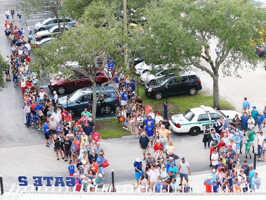 Fans wait outside Hammond Stadium on Friday for the