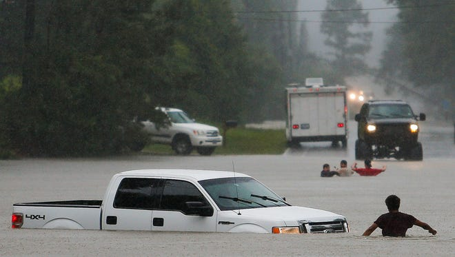 A man, foreground, checks to make sure everyone made it safely out of a truck that flooded when the three men in the background drove around a closed road barrier and lost control of the vehicle in rising flood water Friday, May 27, 2016 in Magnolia, Texas. (Michael Ciaglo/Houston Chronicle via AP)