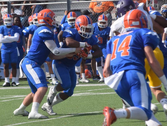 Louisiana College Wildcats quarterback Wayne Griffin (7, left) hands off to Aaron Woods (25, center) in the Wildcats' game against the University of Mary Hardin-Baylor held Saturday.