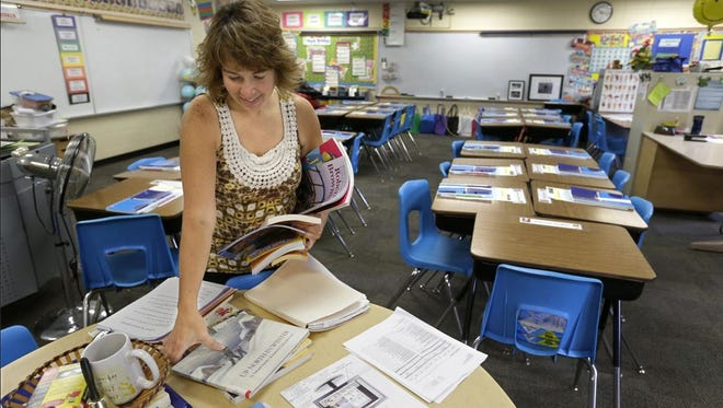 Fourth- and fifth-grade teacher Tricia Retzlaff prepares her classroom Thursday for the upcoming first day of class at Lakeview Elementary School in Neenah. New tests rooted in the Common Core standards for math and reading go in effect this school year.