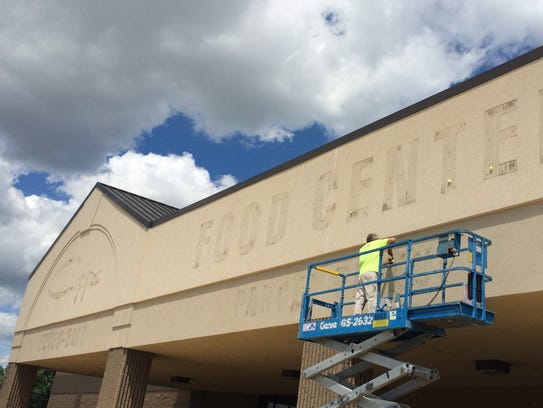 A worker prepares the facade of Copps Food Center in