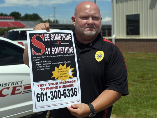 "Petal School District Chief of Police Gavin Guy holds up a poster about the new anonymous texting system called "" See Something, Say Something,"" for students to report activity of possible drug use or planned attacks without fear of reprisal during a press conference at Petal High School on Monday, August 6, 2018. New safety measures will cover all of the Petal School District."