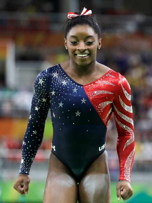 United States' Simone Biles celebrates after completing her routine on the balance beam during the artistic gymnastics women's qualification at the 2016 Summer Olympics in Rio de Janeiro, Brazil, Sunday, Aug. 7, 2016. (AP Photo/Rebecca Blackwell)