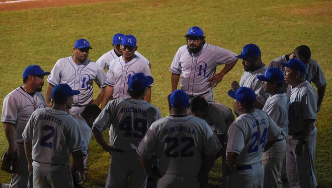 In this June 26 file photo, EMB Rooks players talk things out in a huddle during aGuam Major League Baseball game against the Yigo Astros at Paseo Stadium.
