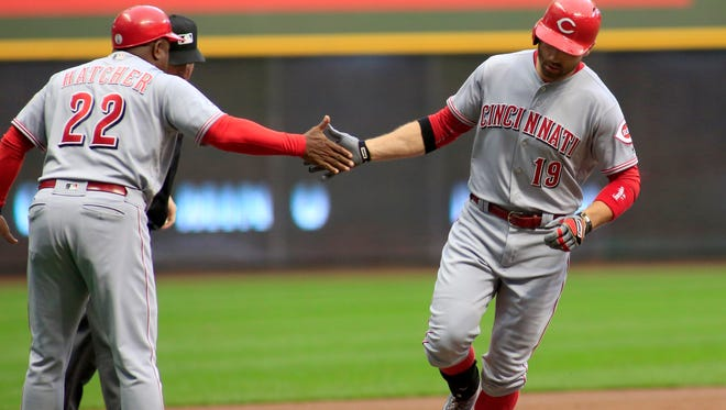 The Cincinnati Reds' Joey Votto, is congratulated by third base coach Billy Hatcher after hitting a two-run home run against the Milwaukee Brewers during the first inning of a baseball game Saturday, Sept. 24, 2016, in Milwaukee.