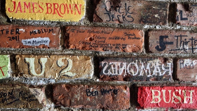 Bricks inside the entrance to Bogart's in Corryville attest to the significant artists who have played there. The club celebrates its 40th anniversary this year.