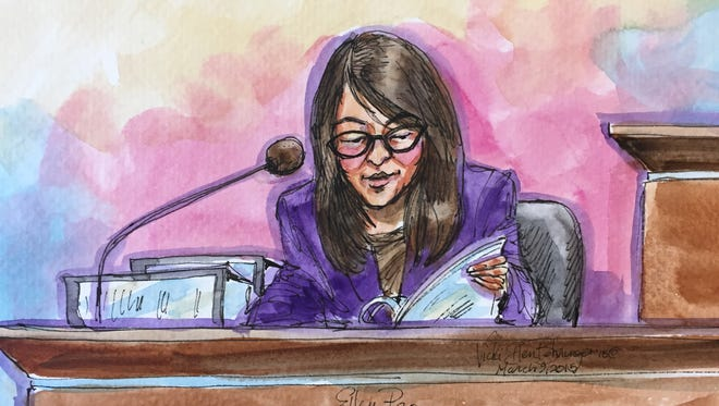 Ellen Pao reads an exhibit on the stand in San Francisco Superior Court.