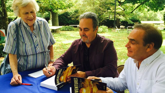 "Autors John Calu (center) and Dave hart sign their book, ""Adventures Along the Jersey Shore""  recently for Nina Walzer of Colts Neck on the Pinelands Preservation Alliance grounds in Southampton"