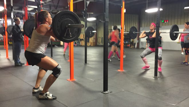 Athletes participate at CrossFit Themis' Respect the Rack fundraiser on Saturday, Oct. 10, 2015. Some athletes wore pink to raise awareness of breast cancer.