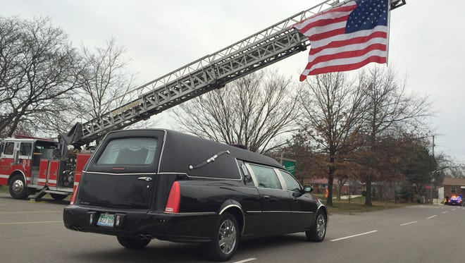 The hearse carrying the casket of Macomb County Treasurer Ted Wahby passes under a St. Clair Shores fire truck holding an American flag after the funeral Dec. 9, 2015 for Wahby, 84, of St. Clair Shores, who died Dec. 5, 2015.