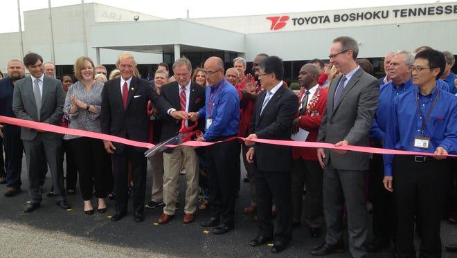 Kimihiko Sumino, center, president of Toyota Boshoku Tennessee, joins Jackson Mayor Jerry Gist and Madison County Mayor Jimmy Harris during a ribbon cutting Thursday at the Jackson facility.