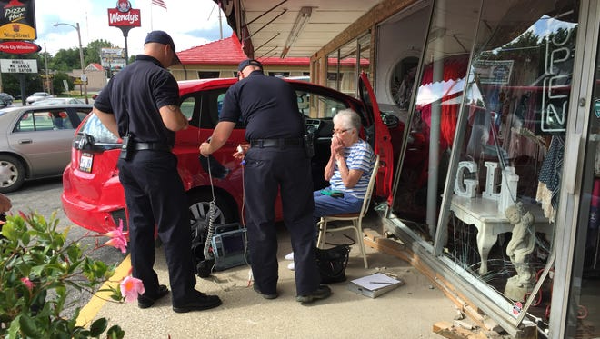 Mansfield Fire Department rescue squad personnel check over the driver of a red Honda that went through the front of Posh Boutique on Lexington Avenue Friday morning.