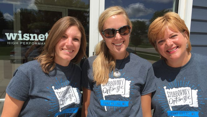 "Wisnet.com employees, from left, Ashley Puetz, Jenny Knuth and Julie Wild model the ""Stubbornly Optimistic"" T-shirts that have created somewhat of a sensation in Fond du Lac."