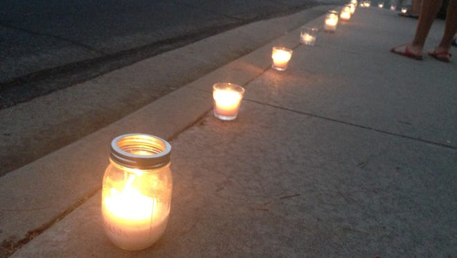 Candles line the street in front of a Mesa church during a Bordertown Justice Coalition protest and vigil for Loreal Tsingine, who was fatally shot by a Winslow police officer.