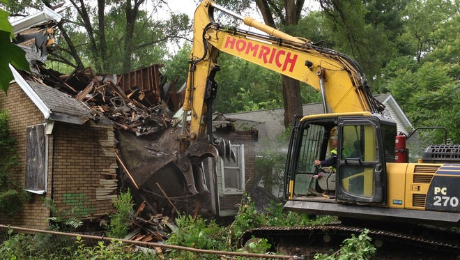 In this June, 2015 photo, a contracted demolition crew from Detroit-based Homrich demolishes a house on Dolphin Street, as part of the city's blighted house demolition program.