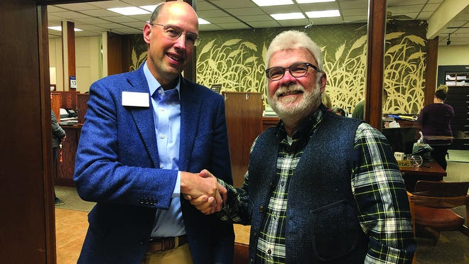 Porter Loomis of Pratt (left), President of The Peoples Bank shakes hands with Steve Bihlmaier (right), President of the former The Farmers Bank of Osborne.