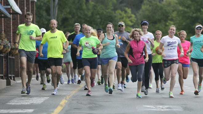 Participants leave Medved Running and Walking Outfitters for their run during the 30th anniversary of the store in Pittsford, N.Y. on Wednesday, August 13 2014.