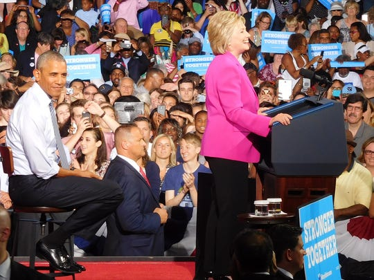 President Barack Obama waits his turn while Hillary Clinton speaks at a campaign rally in Charlotte Tuesday.
